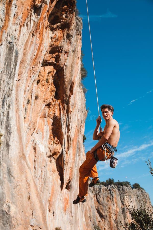 Scalatore che appende sulla corda della sosta sopra le montagne immagini stock