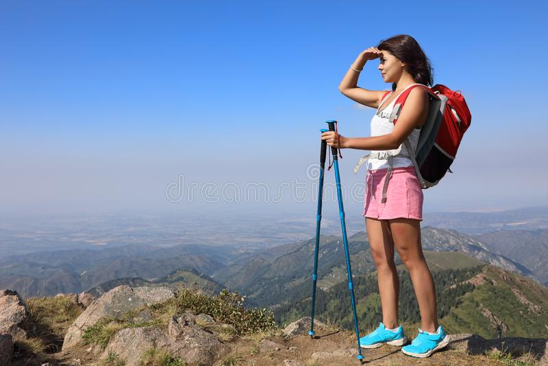 Scalatore che esamina la regione selvaggia sul picco di montagna fotografia stock libera da diritti