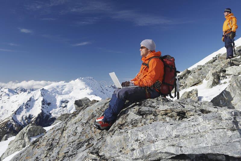 Scalatore di montagna che per mezzo del computer portatile sul picco di montagna immagine stock libera da diritti