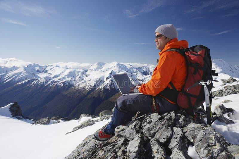 Scalatore di montagna che per mezzo del computer portatile sul picco di montagna fotografie stock