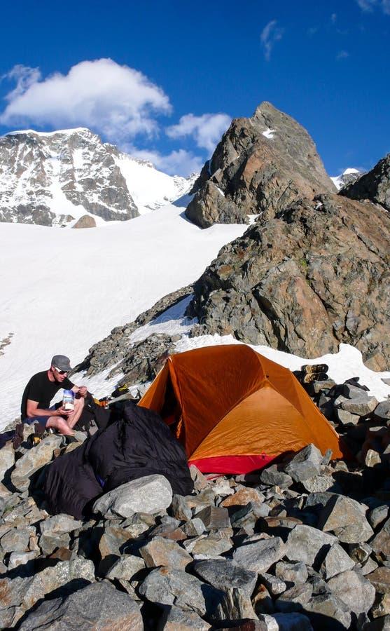 Scalatore di montagna maschio che mangia al campo base da una tenda arancio con un paesaggio spettacolare della montagna intorno  fotografie stock