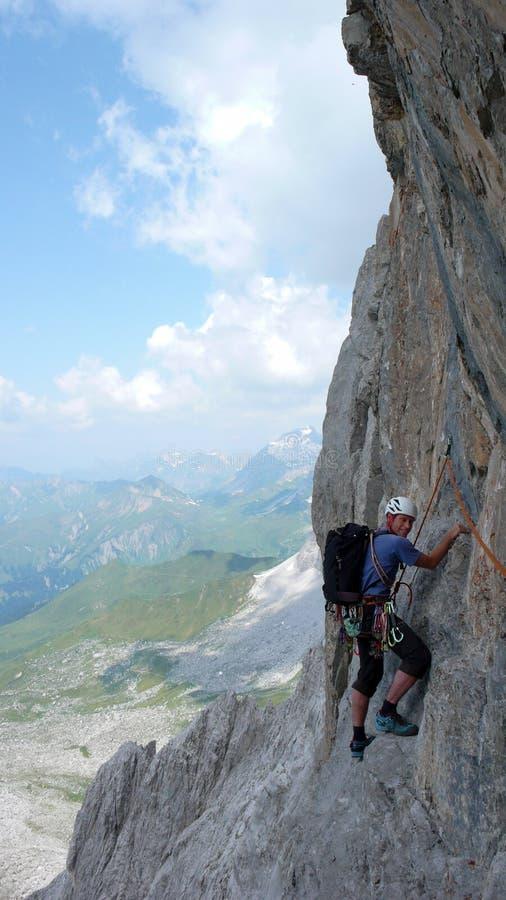 Scalatore di montagna maschio su un itinerario ripido di arrampicata nelle alpi svizzere vicino a Klosters immagini stock
