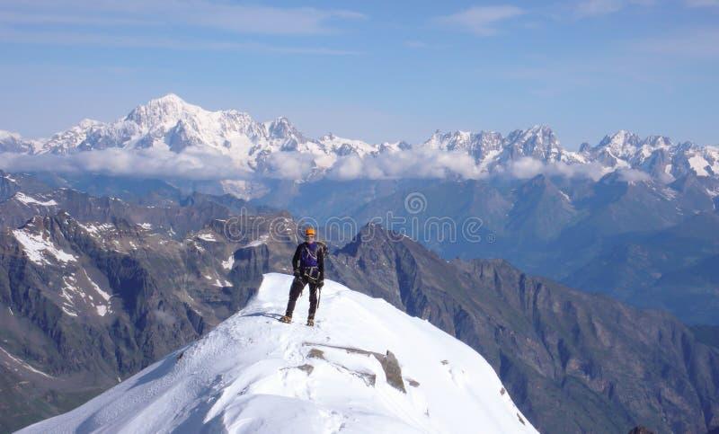 Scalatore di montagna maschio sulla sommità di Gran Paradiso con un grande punto di vista di Mont Blanc dietro lui fotografie stock
