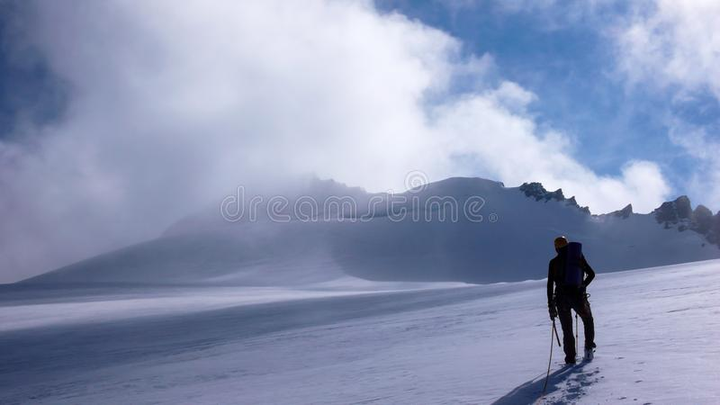 Scalatore di montagna su un grande ghiacciaio nelle alpi con una grande vista dietro lui fotografia stock