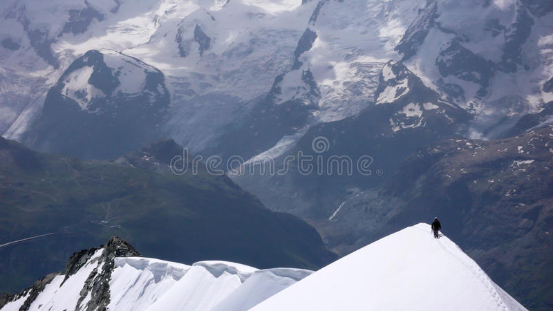 Scalatore di montagna sulla cresta stretta della neve nelle alpi svizzere vicino a Zermatt immagine stock