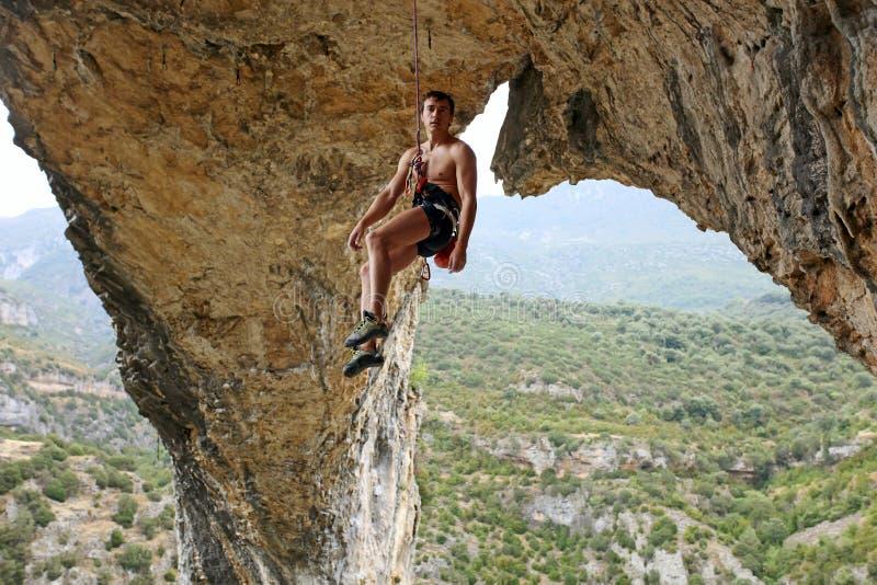 Scalatore di roccia che appende sulla corda immagine stock