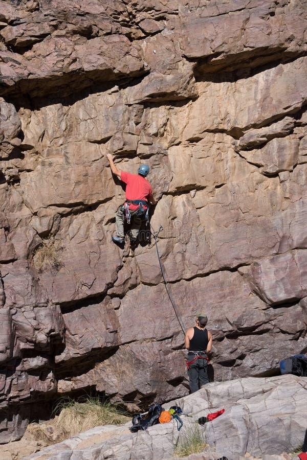 Scalatore di roccia con belaying immagini stock