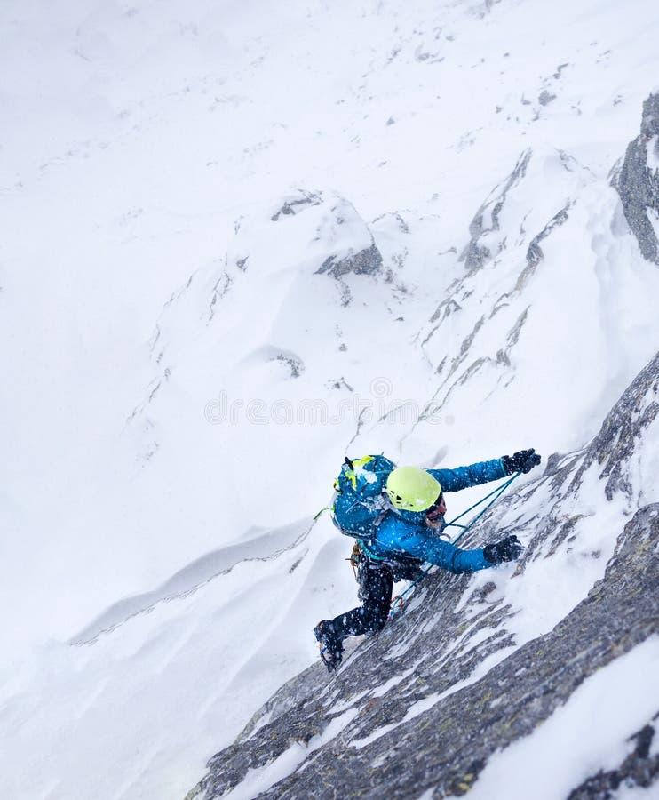 Scalatore femminile nella tempesta durante la salita estrema di inverno fotografia stock