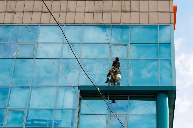 Scalatore industriale che appende sulla corda da bucato e sui lavaggi Windows, costruzione moderna della facciata di vetro fotografie stock