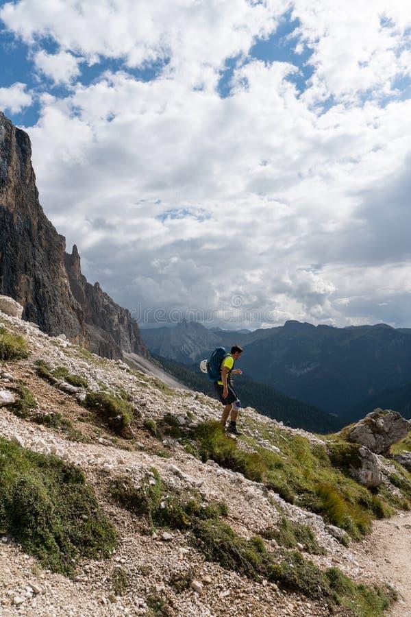 Scalatore maschio con un ginocchio danneggiato che fa un'escursione giù un lato della montagna immagini stock libere da diritti