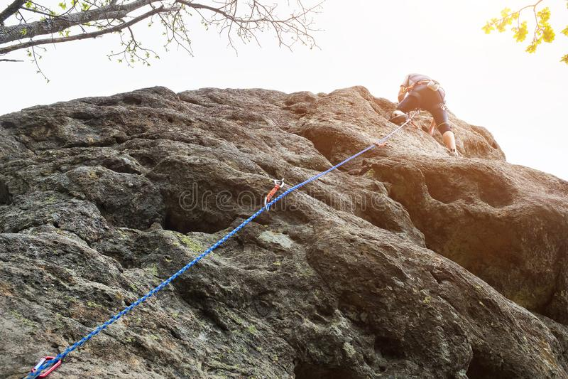Scalatore maschio, giovane uomo-scalatore che scala un itinerario difficile su una scogliera Lo scalatore scala una parete roccio fotografie stock
