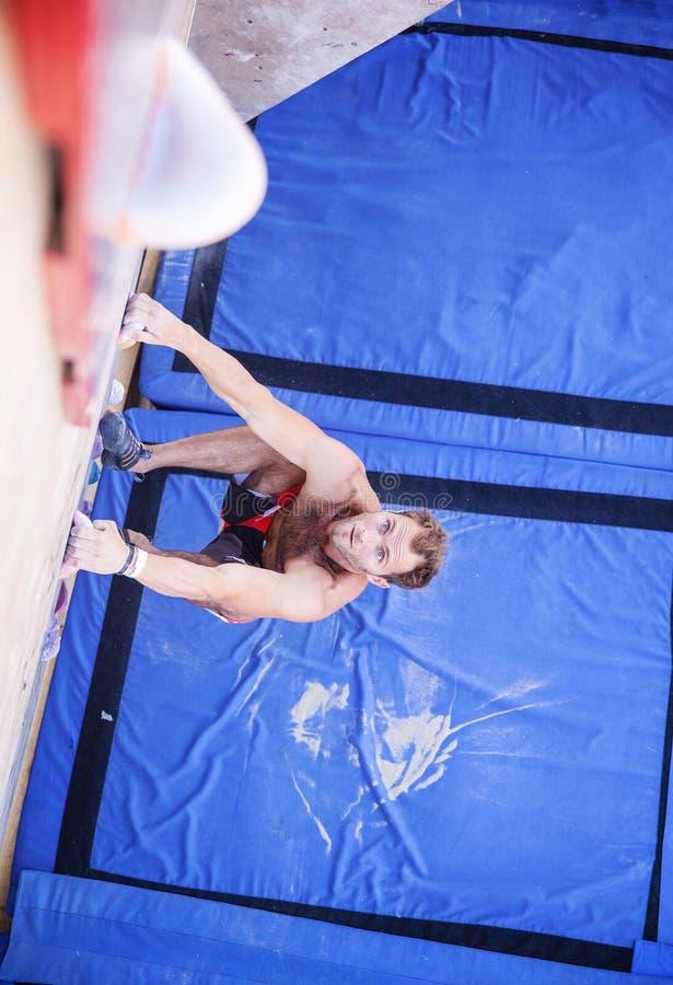 Scalatore maschio prima di un salto sulla parete rampicante artificiale immagine stock