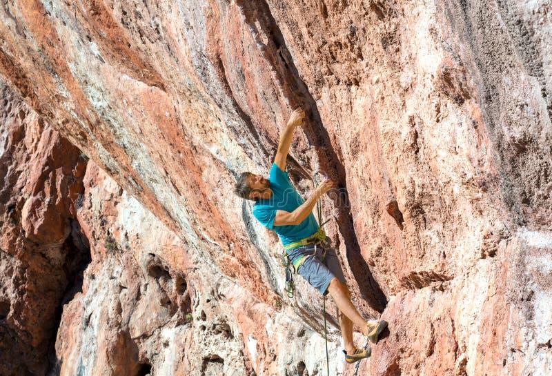 Scalatore maschio sull'alta parete di pietra naturale arancio immagine stock libera da diritti