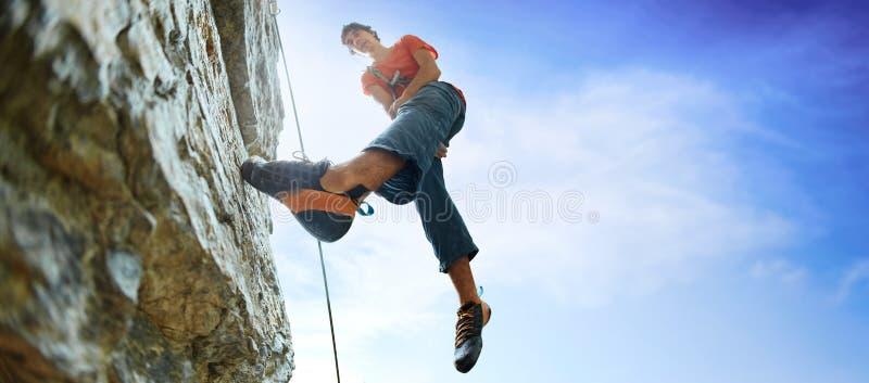 Scalatore maschio sulla scogliera contro un cielo blu immagini stock libere da diritti
