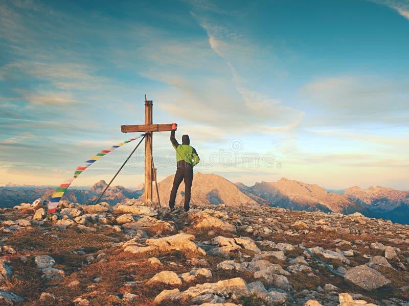 Scalatore solo dell'uomo vicino all'incrocio della sommità sul picco, alpi della dolomia, Austria Sera ventosa soleggiata immagine stock
