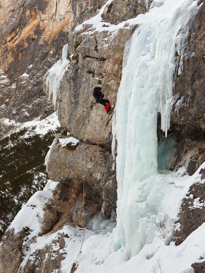 Scalatore su ghiaccio che Rappelling giù la cascata congelata immagine stock
