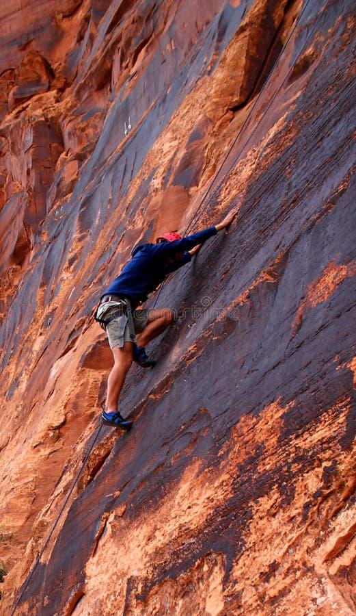 Scalatore sulla parete rossa della roccia vicino a Moab/Utah fotografia stock libera da diritti