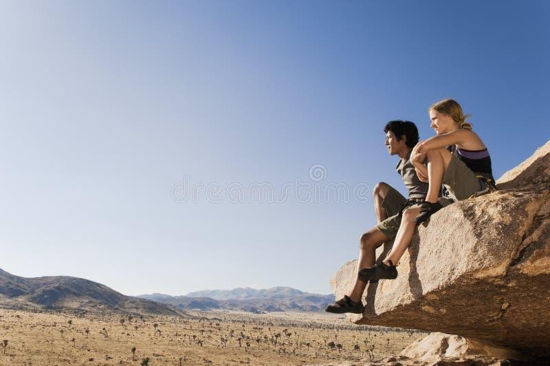 Scalatori che si siedono sulla roccia contro il cielo blu fotografia stock