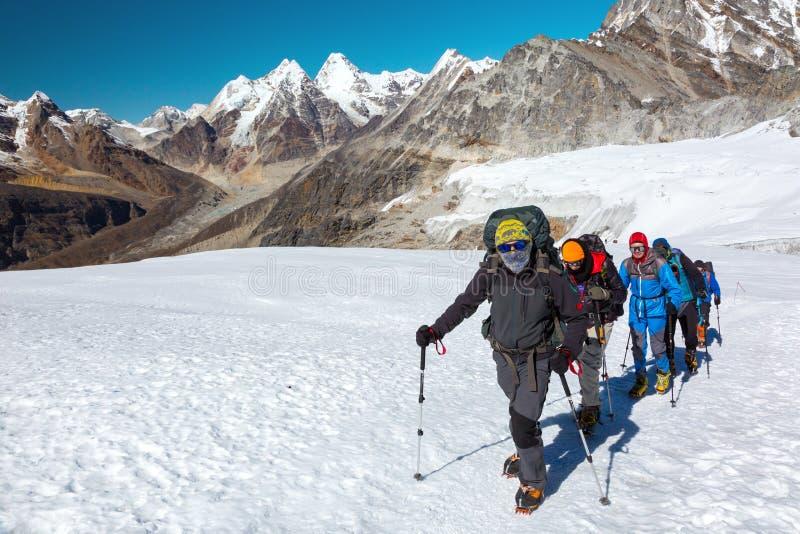 Scalatori di montagna severi in vestiario di protezione del tempo sul ghiacciaio fotografia stock