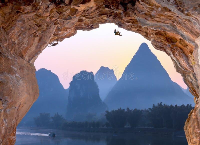 Scalatori estremi della caverna profonda di livello su alba in montagne della Cina fotografie stock