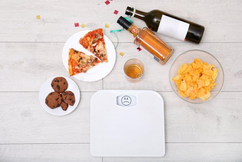 Scale, alimenti industriali ed alcool di Digital sul pavimento di legno dopo il partito fotografia stock