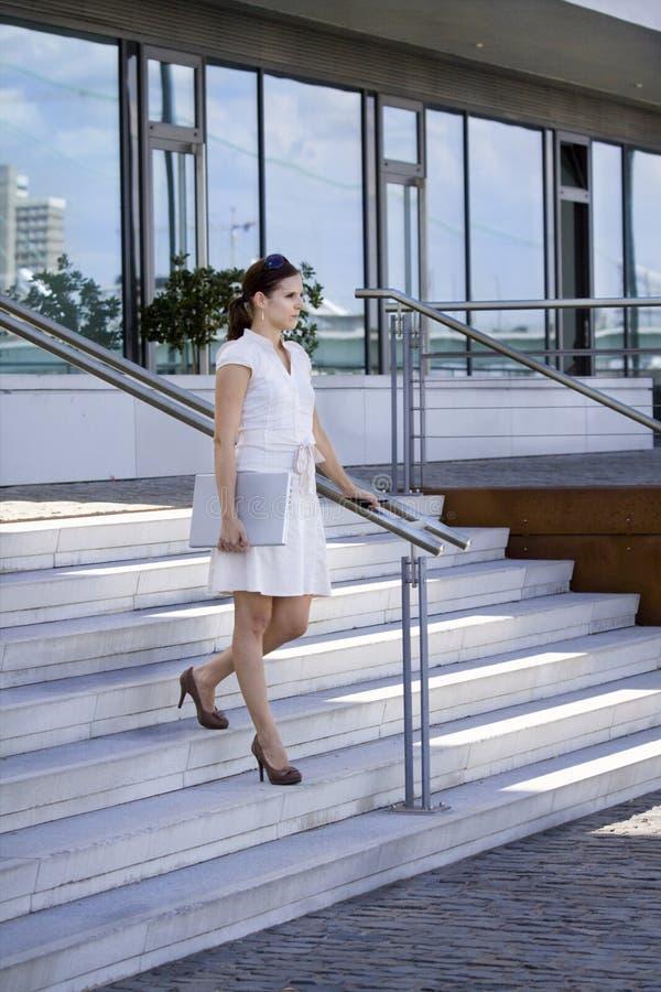 Scale ambulanti della signora di affari con il giro del telefono mobile immagine stock