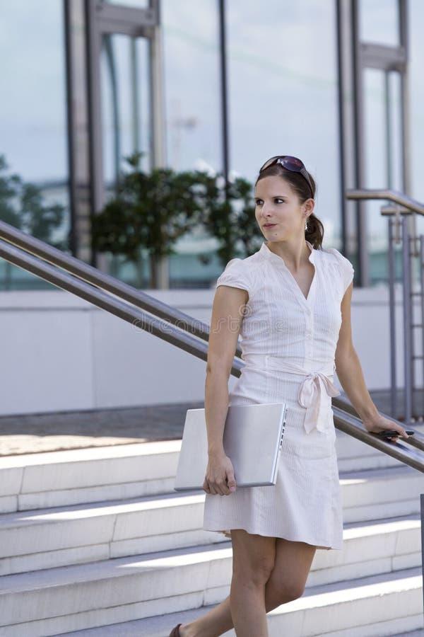 Scale ambulanti della signora di affari con il giro del telefono mobile fotografia stock libera da diritti