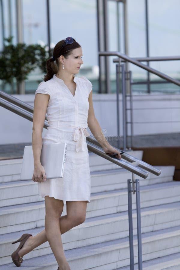 Scale ambulanti della signora di affari con il giro del telefono mobile fotografie stock
