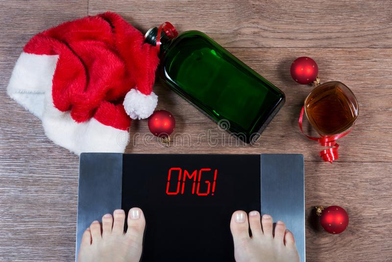 Scale di Digital con i piedi femminili loro e sul omg del segno! circondato dalle decorazioni, dalla bottiglia e dal vetro di Nat fotografie stock libere da diritti
