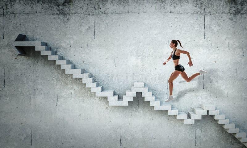 Scale di pietra rampicanti femminili del giovane atleta che illustrano sviluppo di carriera e concetto di successo Media misti fotografia stock libera da diritti