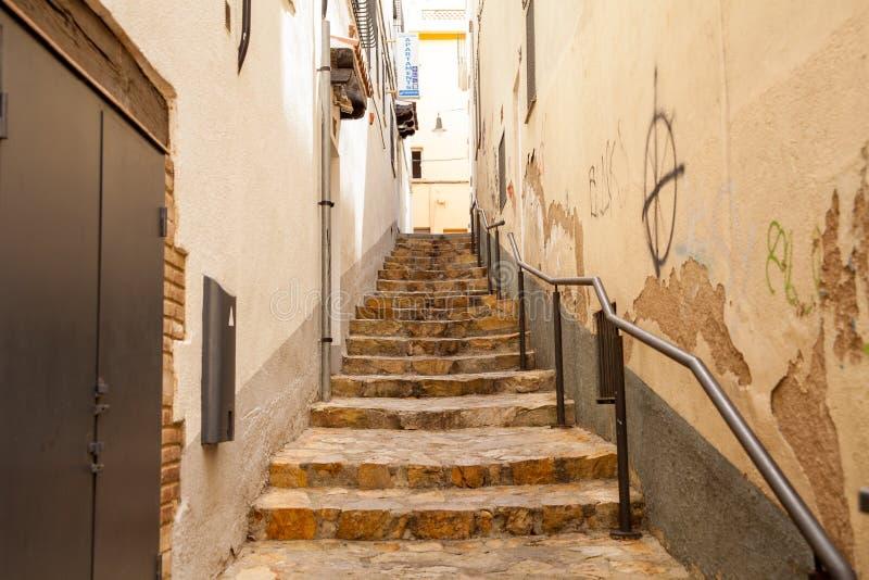 Scale fra le case vicino alle vie strette di Lloret de Mar fotografia stock