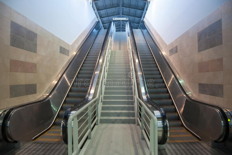 Scale mobili nel movimento in una stazione ferroviaria, andante dalla metropolitana al binario immagini stock