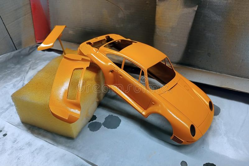 Scale model hobby. Paint the spoiler, trunk lid and toy body in a bright orange color. Car sports assembly plastic kit modeling modelist vintage style brush joy stock image
