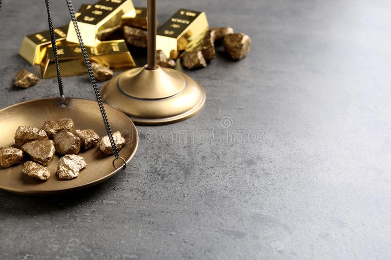 Scale pan with gold lumps on grey table. royalty free stock images