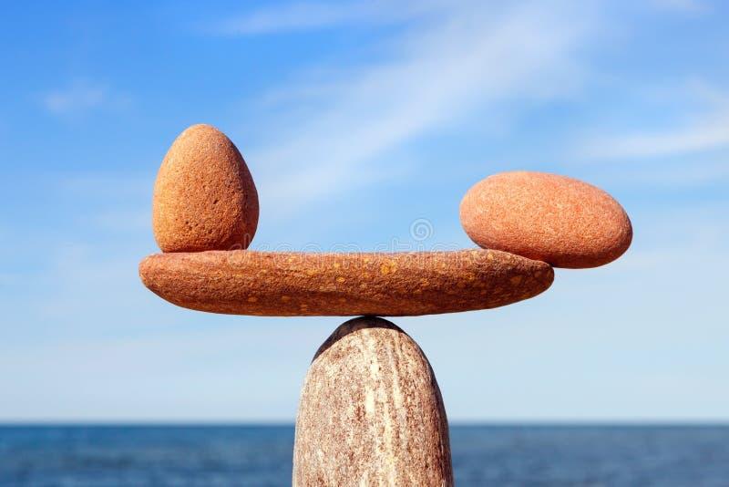 Scale simboliche delle pietre, illuminate dal sole di sera, contro il mare, primo piano Pro - e - concetto di contro fotografia stock libera da diritti