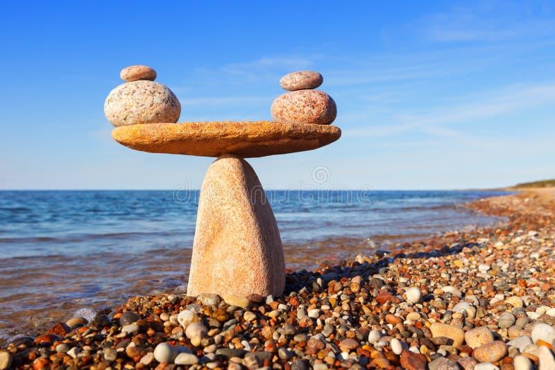 Scale simboliche delle pietre, illuminate dal sole uguagliante, contro il mare Pro - e - concetto di contro fotografia stock libera da diritti