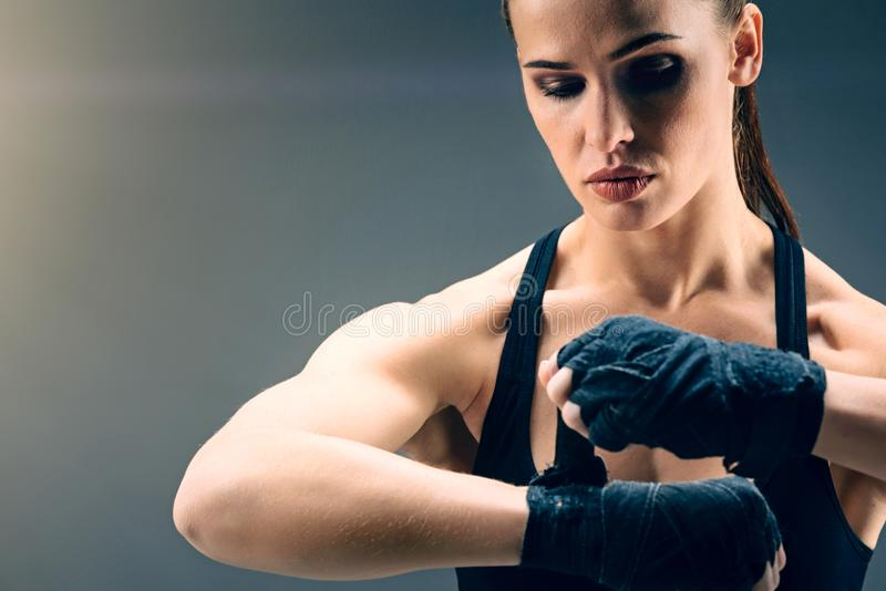 Scaled up look on beautiful female boxer wrapping hands royalty free stock photo