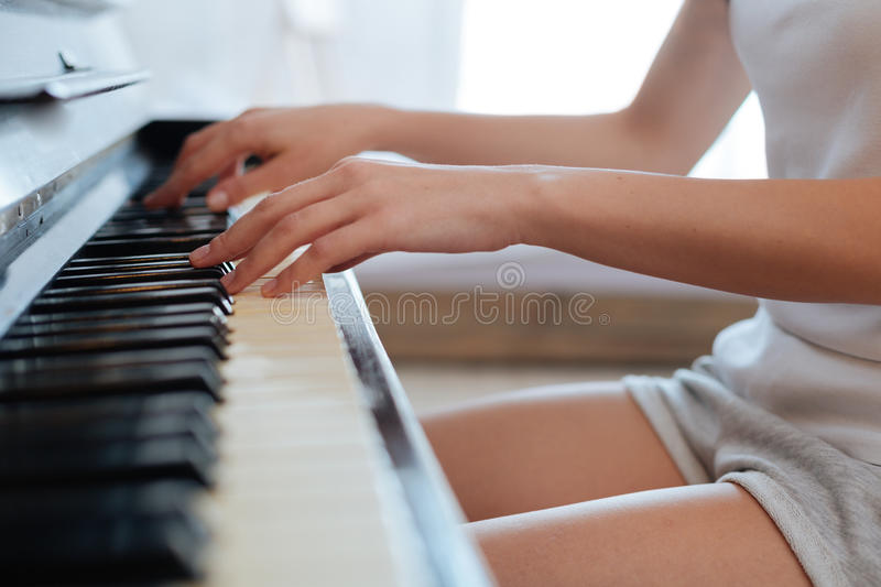 Scaled up shot of young woman playing piano at home stock images