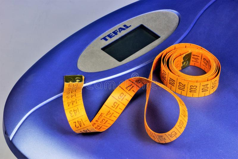 Scales and centimeters-control figures, weight in fitness. Obesity, weight management and healthy eating. Attractive figure is a royalty free stock photo