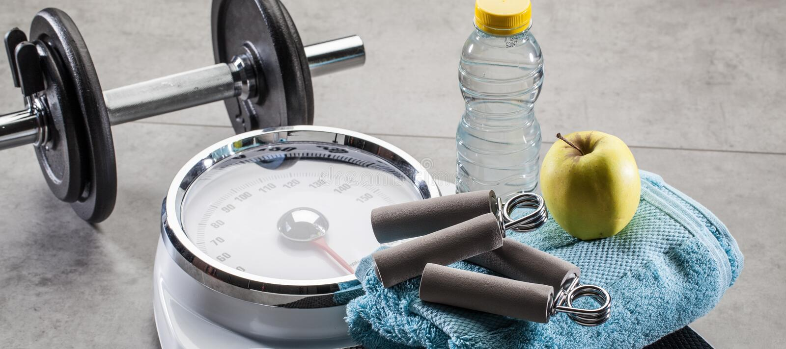 Scales for fitness, workout and weight control on gym floor. Scales for fitness, workout and weight control with hand grips and dumbbells, bottle of water and stock photography