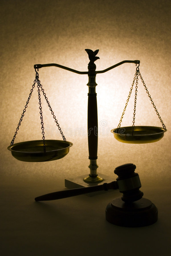 Scales of justice. Conceptual image of light illuminating unequal retro style weighing scales with judicial hammer in foreground stock photos