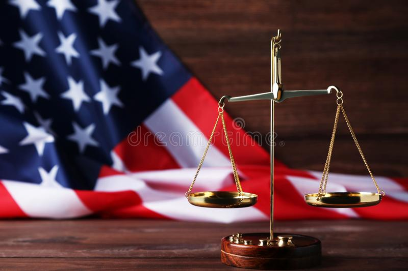 Scales of justice with american flag. On brown wooden table royalty free stock images