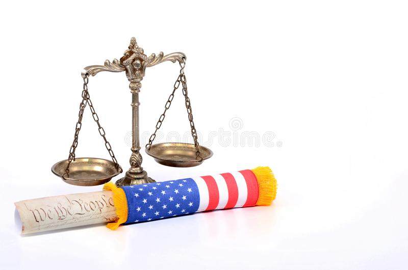 Scales of justice and US Constitution rolled up with American flag. Law and justice concept royalty free stock photos