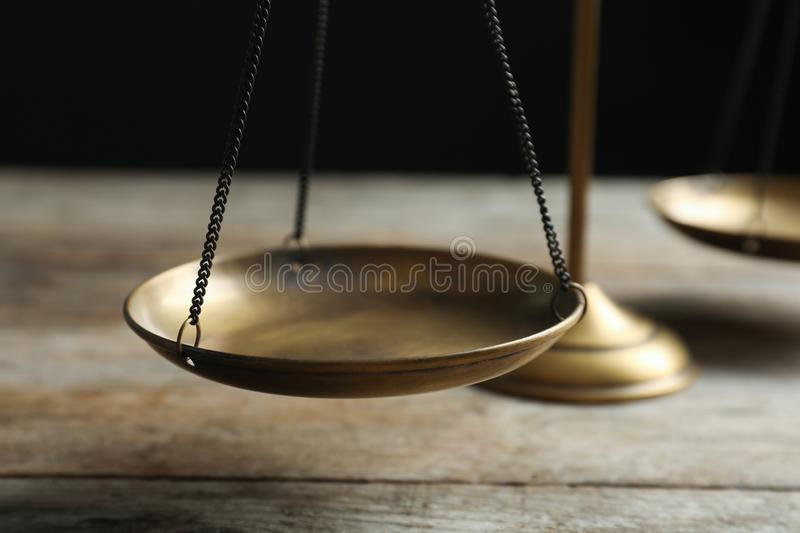 Scales of justice on wooden table against dark background. Closeup. Law concept royalty free stock photography