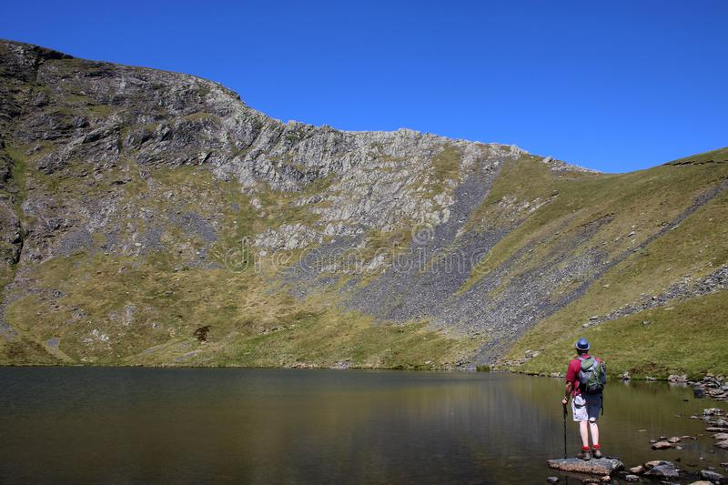 Scales Tarn, Blencathra and view to Sharp Edge. Male fellwalker stood on a rock at edge of Scales Tarn on Blencathra also known as Saddleback in the English Lake stock photography