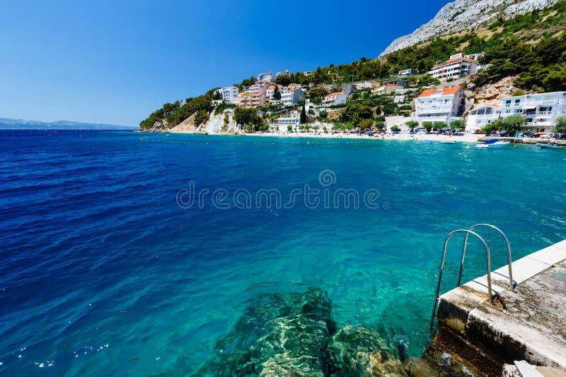 Scaletta del metallo sulla spiaggia e sul mare di azzurro immagini stock