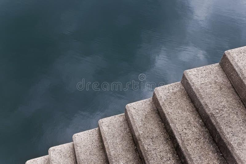 Scalini di calcestruzzo che portano a un lago fotografia stock