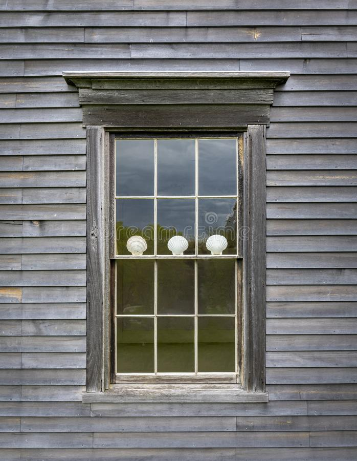 Scallop Shells in a Colonial House Window. An old New England clapboard house exterior with window with three white Scallop shells stock photo