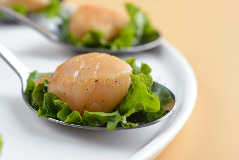 Scallop snack on spoon stock images