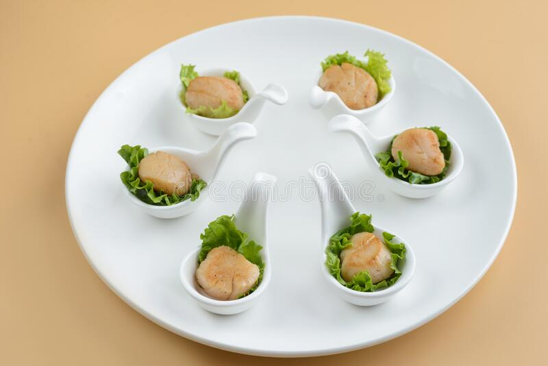 Scallop snack on spoon royalty free stock images